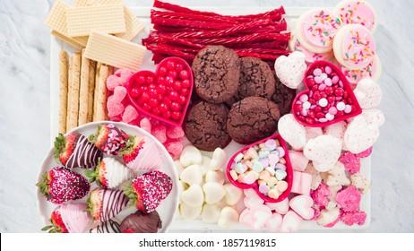 Plat lay. Pas à pas. Carte de fromage avec bonbons et biscuits pour la Saint-Valentin.