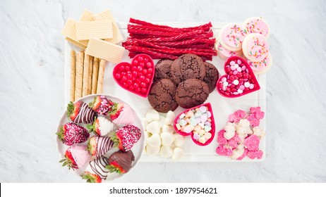 Flat lay. Step by step. Cheese board with candies and cookies for Valentines Day.