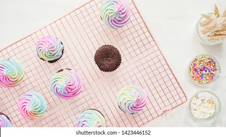 Flat lay. Step by step. Frosting unicorn chocolate cupcakes with rainbow color buttercream frosting.