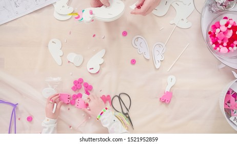 Flat lay. Step by step. Little girl making unicorn craft out of white and pink paper foam.