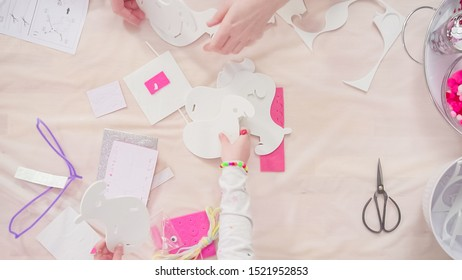 Flat lay. Step by step. Mother and daughter making unicorn craft from paper foam.