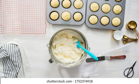 Flat lay. Step by step. Scooping a white buttercream frosting into a piping bag to decorate vanilla cupcakes.