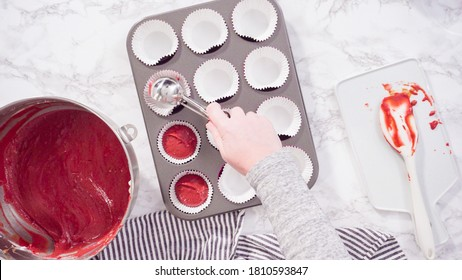 Flat lay. Step by step. Scooping cupcake batter into foil cupcake cups to bake red velvet cupcakes.