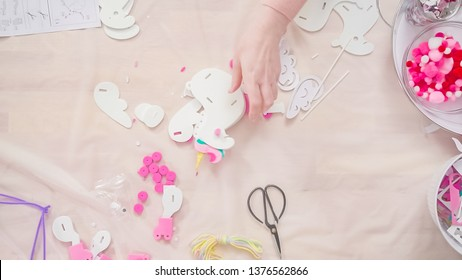 Flat lay. Step by step. Woman making a unicorn figurine out of the white and pink paper foam.