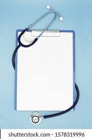 Flat lay of stethoscope and writing pad paper clip board on light blue background with copy space, healthcare and medical concept, top view photo.