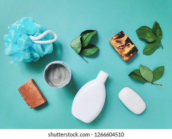 Flat lay still life bath products photography. Spa cosmetics set for skin and hair care. Herbal bath products on a turquoise background. Brown soap, shampoo, kaolin, blue sponge and green leaves