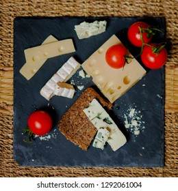 Flat lay. Still life french style. Assortment of cheese served with bread and fresh tomatoes on a red and white plaid tablecloth and two glasses of white wine. Picnic mode