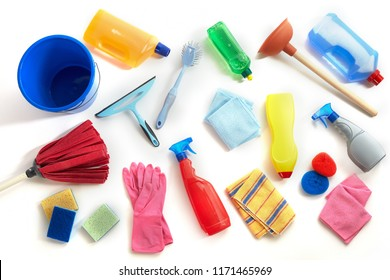 Flat lay still life of scattered cleaning supplies for the house with mop, cloths, plunger, sponges, plastic containers and bucket isolated on white