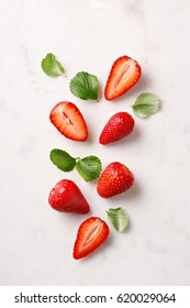 Flat lay strawberries on a marble background. Sliced and whole. Top view