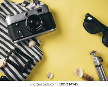 Flat lay style. Yellow background with travel accessories camera, Mikey sailor points and shell with place for text