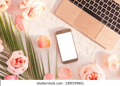 Flat lay of stylish composition with laptop, mobile phone. tropical palm leaf, pink rose flowers, on pastel background with shadows and sun light. Top view of feminine rose gold desk with blank screen