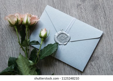 Flat lay stylish mockup photo with envelope with seal wax and roses bouquet flowers on the light wooden background. Feminine photo for blog and website.