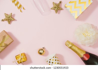 Flat lay stylish set: champagne, gift, christmas balls and golden holiday decoration. Flat lay, top view.