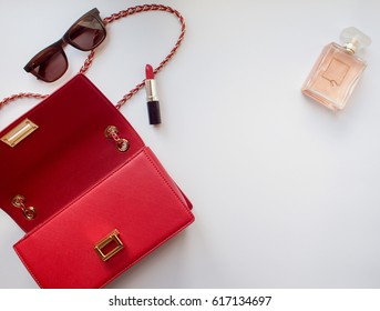 Flat lay of stylish woman accessories, red handbag clutch, sunglasses,lipstick and perfume on white background with copy space