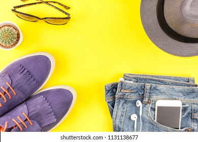 Flat lay of suede shoes, blue jeans, grey hat, cactus and smartphone headphones on bold yellow paper background with copy space. Overhead view of woman casual outfit. Trendy hipster look top view