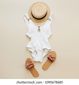 1e1ca38d24 Flat lay summer fashion composition. Women's swimsuit, straw and slippers  on pastel beige background. prepare accessories ...