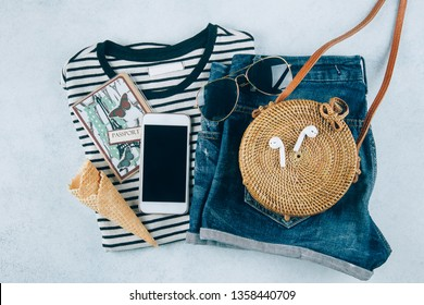 Flat lay with summer women's clothing and accessories. Striped t-shirt, blue denim shorts, fashionable organic rattan bag. Vacation, travel concept. Top view