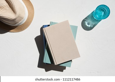 Flat lay of sun hat with a stack of books and a glass of water