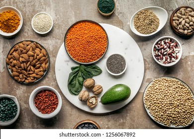 flat lay of superfoods, legumes, nuts and avocado on textured rustic background