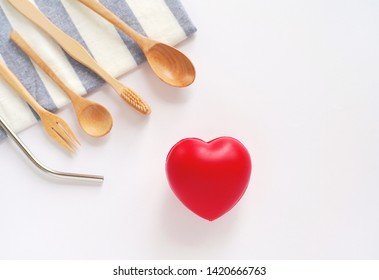 Flat lay of sustainable products, wooden spoon, stainless straw on table cloth with red heart on white background, eco friendly and zero waste concept