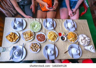 Flat lay table with tofu, fried eggs, spring rolls, mixed noodles, starters and pastries over yellow table cloth and people sitting around, top view. Holiday gathering, vegetarian party concept