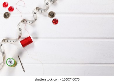 Flat lay or table top of sewing equipment with buttons, thread and tape measure with white space for text or Image