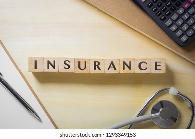 Flat lay, table top view word INSURANCE on cubes with stethoscope, notebooks, paperwork,  wooden desk background. Healthcare policy, security, personal safety plan, business investment concepts.