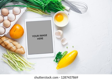 Flat lay with Tablet computer with fresh vegetables on white background, copy space