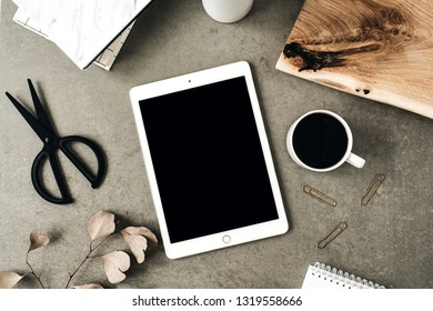 Flat lay of tablet with copy space screen mock up. Top view home office desk workspace decorated with eucalyptus, wooden board and stationery. Social media / blog / website mockup concept.