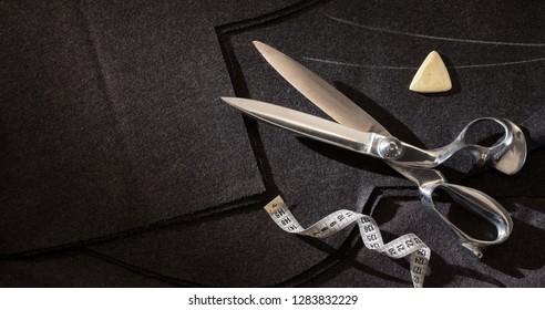 Flat lay tailor scissors,   black fabric , tape measure centimeter on black fabric background