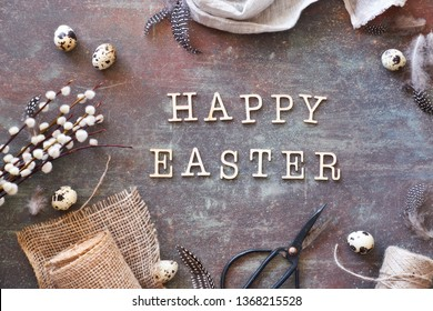 "Flat lay with text ""Happy Easter"" made of wooden letters with natural springtime decorations around: quail eggs, sackcloth, white flowers, cord and linen towel"