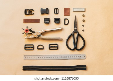 Flat lay of tools and accessories for bags of clothes making. Top view of  eyelet puncher, scissors, pieces of leather, ruler and other devices for hand work