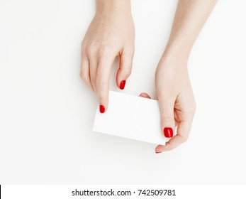 Flat lay, top view. Beauty and fashion concept. Beautiful female hands with red manicure. Minimal style. Minimalist photography. Pale composition with girl's hand holding card on white background