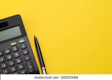 Flat lay or top view of black pen with calculator on vivid yellow background table with blank copy space, math, cost, tax or investment calculation.