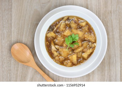 Flat lay (top view) Braised Fish Maw in Red Gravy, Chinese style soup in white bowl with wooden spoon on wooden background