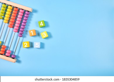 Flat lay, Top view of bright colored wooden bricks and abacus toy background with copy space for text, Numeral cubes with numbers 1 to 5 & colorful abacus, Child development, early math skills concept