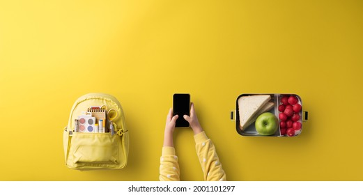 Flat lay top view of child hands with smartphone, healthy snack and back to school concept.