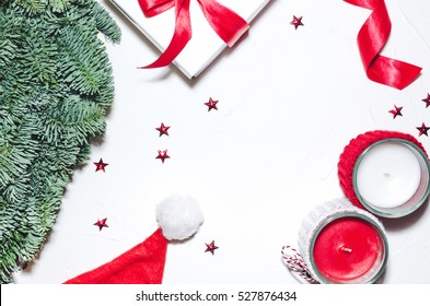 Flat lay, Top view Christmas composition isolated on white background. Natural green pine wreath, white gift box with red fabric tape, spiral ribbon, stars confetti, candels. Xmas background.