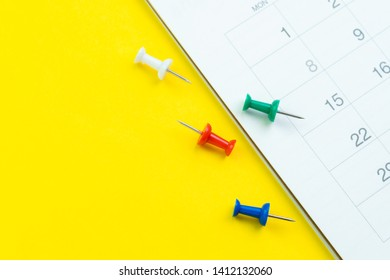 Flat lay or top view of clean white calendar with thumbtack or pushpin on vivid yellow background with copy space using as reminder, vacation plan, business organizer or meeting schedule concept.