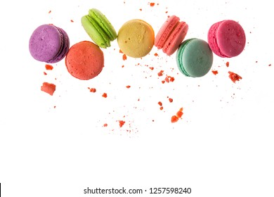Flat lay, top view. Close up. French macaroons isolated on white background. Cookies falls mixed with crumbs. Copy space.