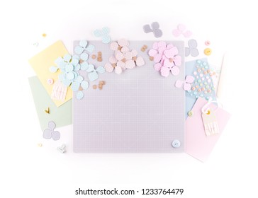 Flat lay, top view craft table desk. Workspace with mat for cutting, scissors, cardstock, paper, pencils on white background. Make floral wreath decor.
