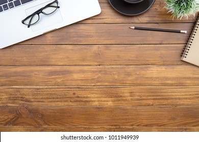 Flat lay of top view desk work table with computer laptop and stationary in home office on antique brown wood table includes copyspace for add text or graphic
