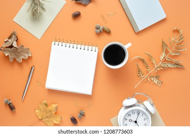 Flat lay, top view feminine work office table desk. Workspace with dry autumn leaves, blank notebook, cup coffee and office supplies on orange background