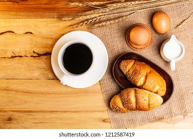 Flat lay, top view fresh bread with wheat, cereal and egg,milk , cofee on wooden background