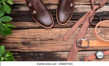 Flat lay, top view, men fashion clothing set and leather accessories on rustic wooden background include brown shoes, tie, belt, bracelet and watch.