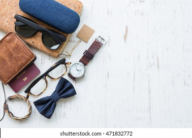 Flat lay, top view, men's accessories and essential travel items with space for text or object on white rustic wooden background