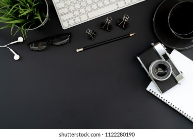 Flat lay of top view modern black desk work table with computer laptop,retro film camera and stationary in home office includes copyspace for add text or graphic