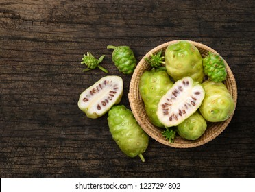 Flat lay (top view) Noni or Morinda Citrifolia fruits in basket with sliced on old wood background