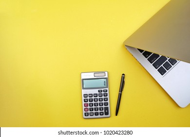 Flat lay, top view office table desk. Workspace with calculator, black pen , laptop on the yellow background.Copy Space for text,Blank word