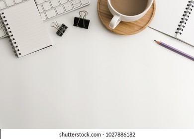 Flat lay, top view office table desk. Workspace with blank notepad, keyboard, office supplies, pencil, green leaf, and coffee cup on white background.